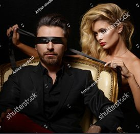 beautiful blonde hair lady blindfold a man wearing a black suit
