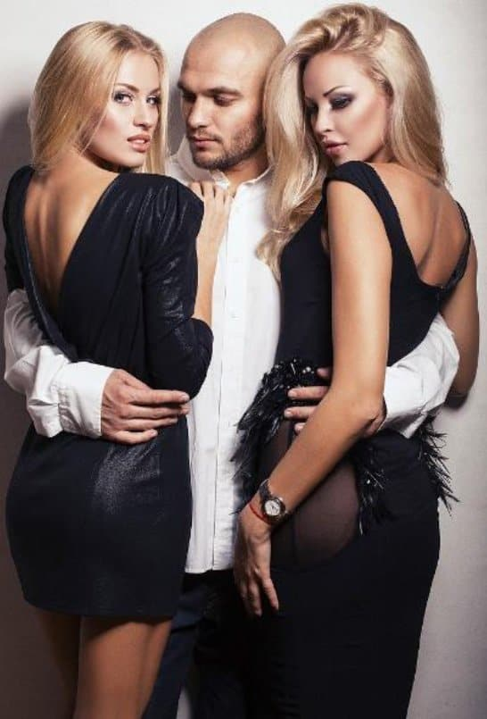 a man wearing white longsleeve business shirt and women wearing black sexy dress for threesome intimacy