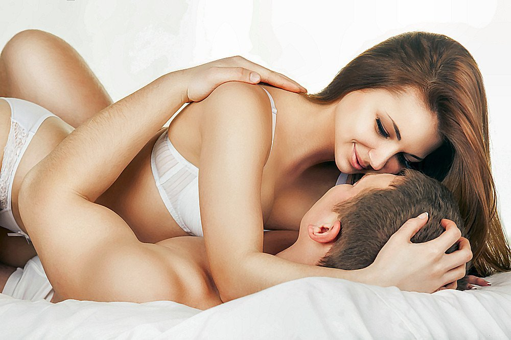 man and woman in white underwear laying on top of each other on the bed