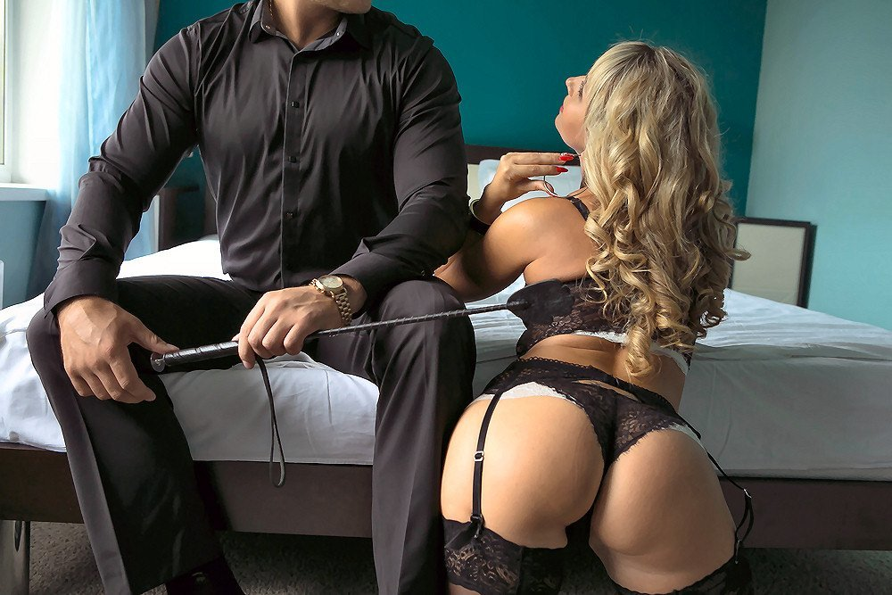 Submissive blonde woman in black lingerie kneeling beside her master with a rubber whip