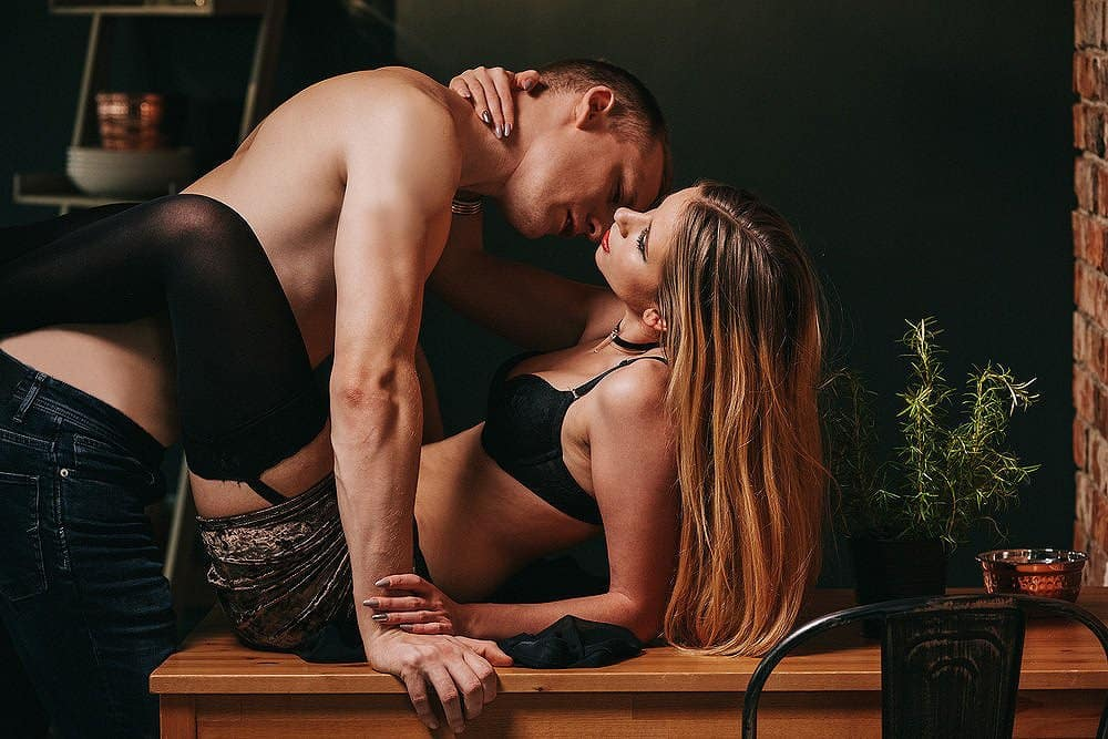 Hot woman in black set of sexy garments wrapped her long legs around the waist of a shirtless man