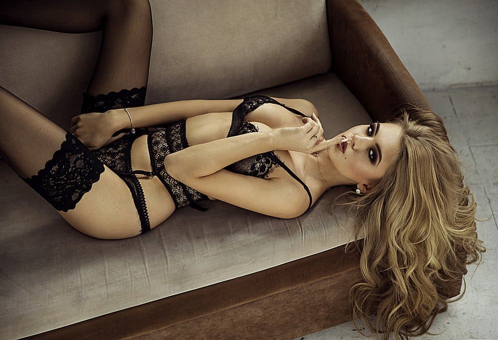 Seductive woman in a black lingerie showing off her sexy body on a brown loveseat