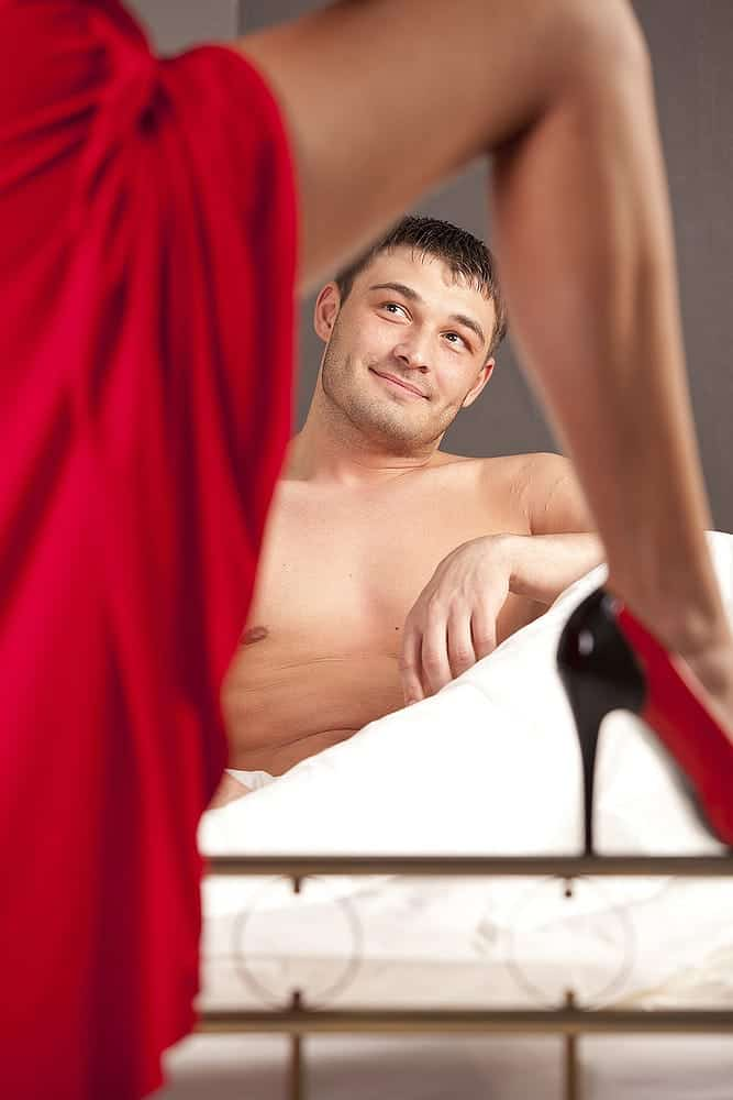 topless man waiting on the bed with a sexy lady wearing red satin and red heels
