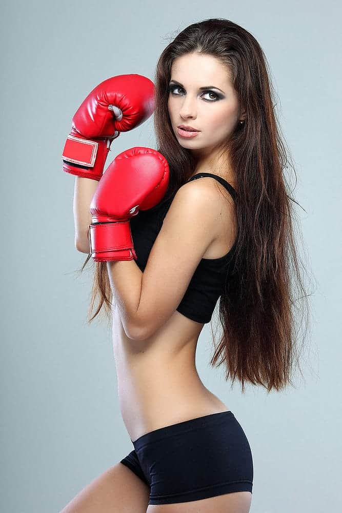 long hair woman wearing a seductive black bralette and boyshort and red boxing gloves