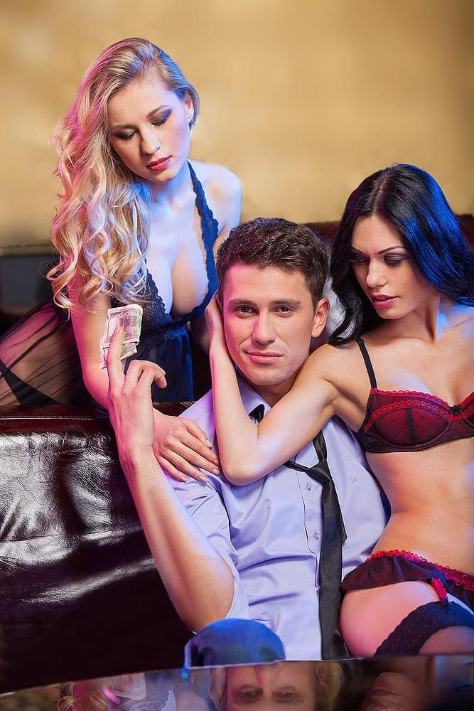 sensual women wearing a mesh lace nightgown and red lace lingerie teasing a man
