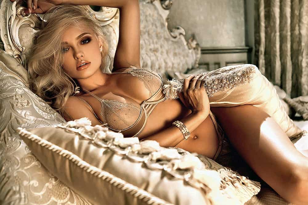 sensual lady wearing a gold sexy see through lingerie lying down