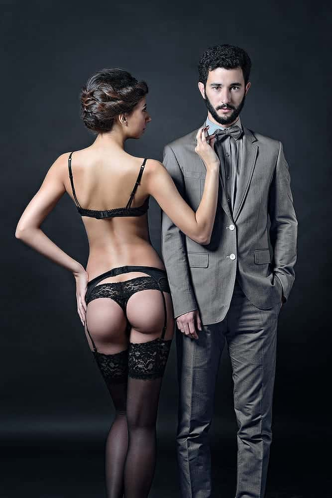 woman wearing black sexy lace lingerie with a man wearing business suit
