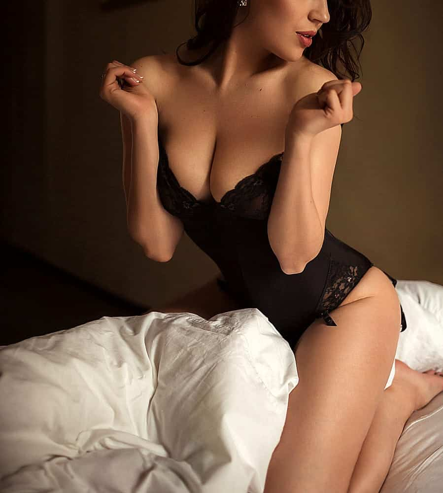 alluring black haired lady wearing sexy black lace bodysuit sitting on the pillow