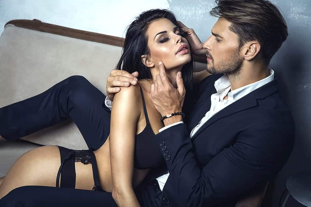 man with a beautiful lady wearing black sexy lingerie and garter belt