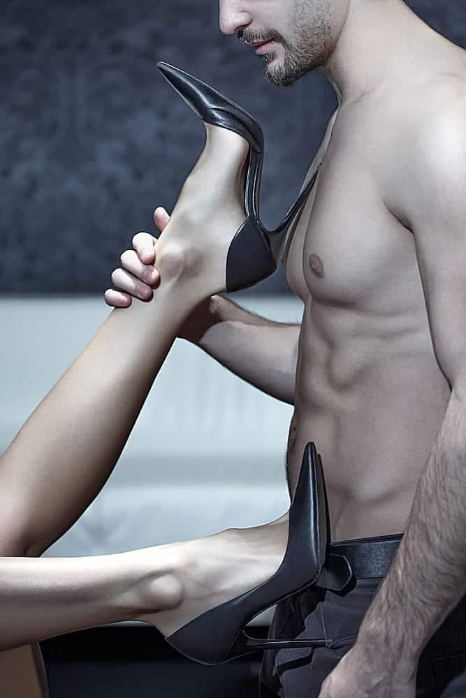topless man holding the woman's feet wearing a black sexy heels