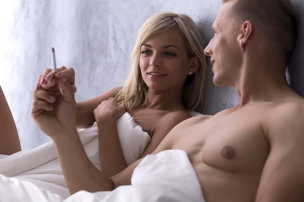 man and woman smoking after sex