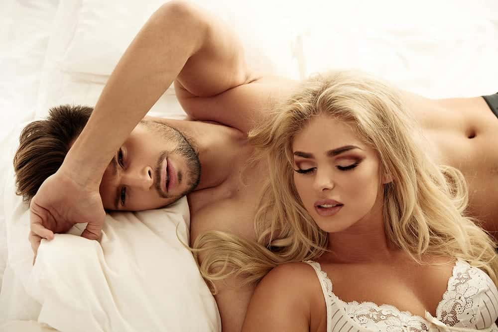 sensual and attractive couple relaxing on bed