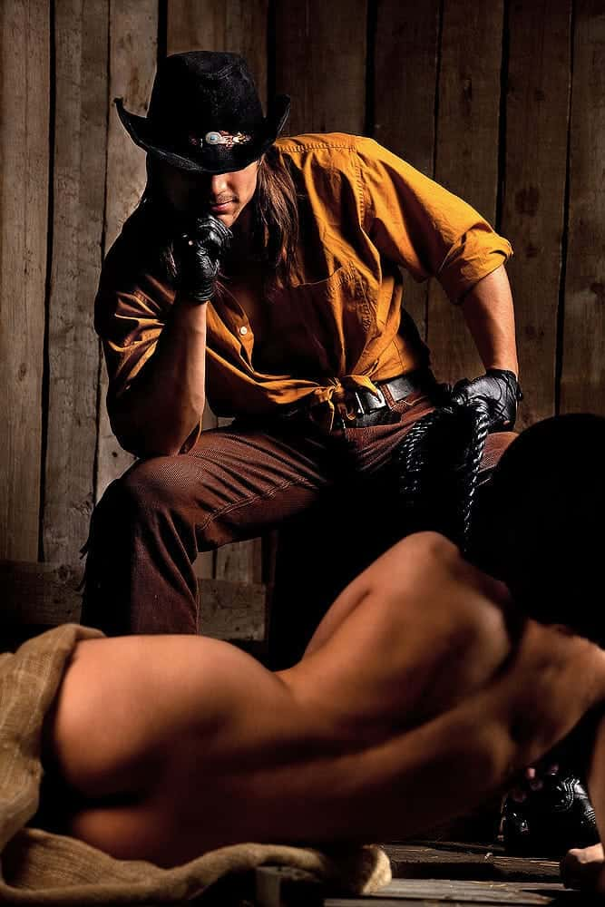 cowboy man with hot and sexy naked woman lying down exposing her ass