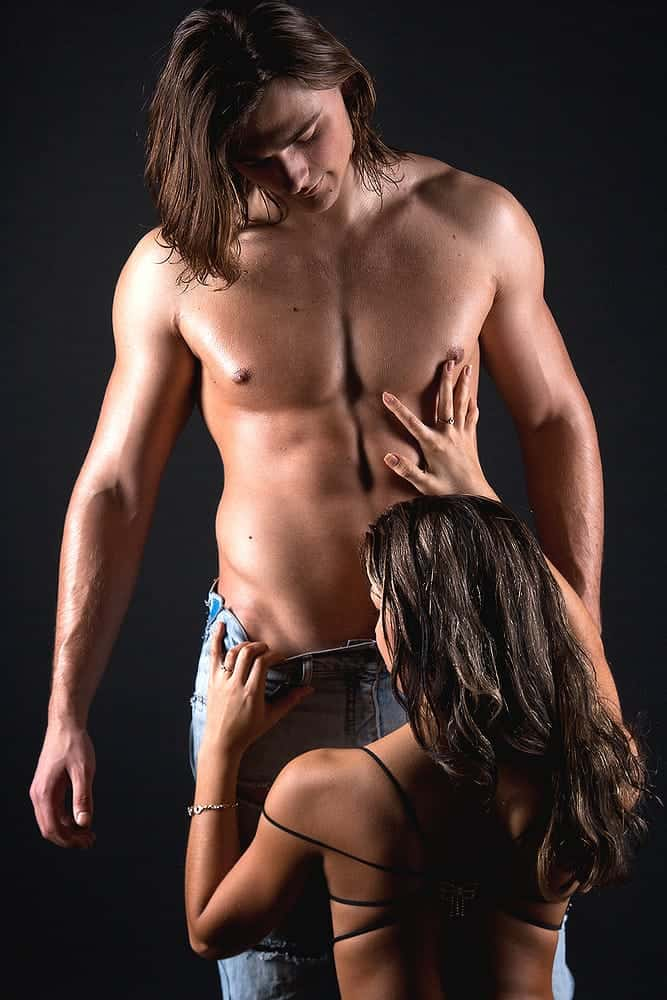 woman kneeling and touching the standing half naked man