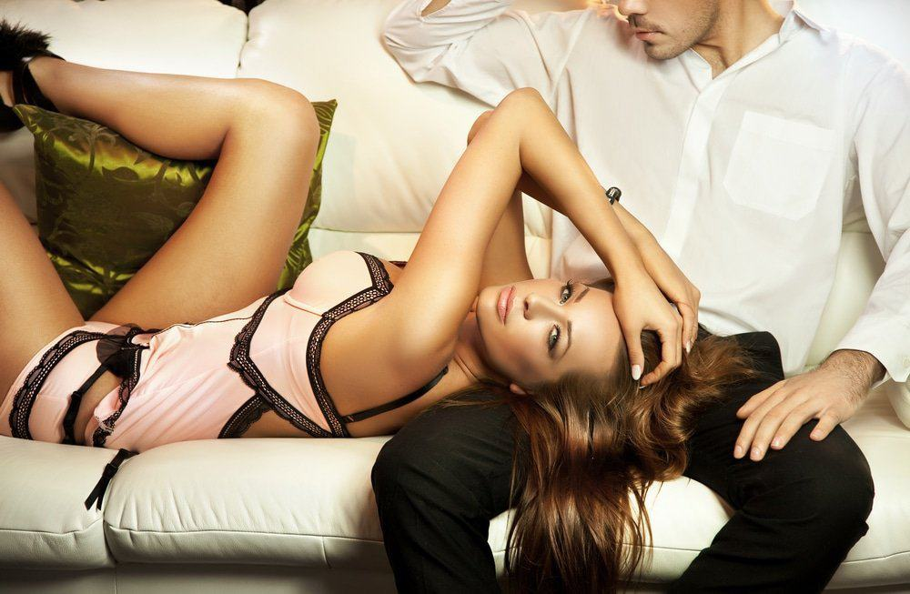 Woman in her pink and black lace lingerie on the lap of a man in white shirt and pants