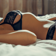 woman wearing black sexy see through lingerie lying on the bed