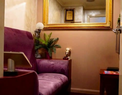 purple velvet couch and a mirror with gold frame on the left