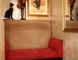 small red, black and beige velvet sofa placed near a black cat decor