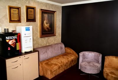 coffee and water station with purple and brown velvet couch and 2 single velvet chairs