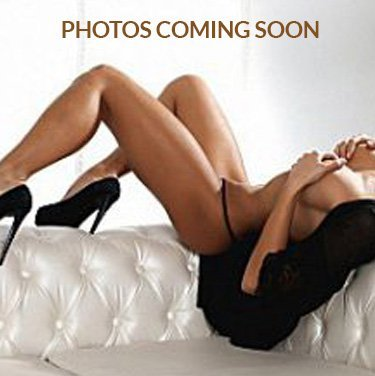 Erotic woman in her black shoes and untied black robe covering her breast with hands lying on a sofa